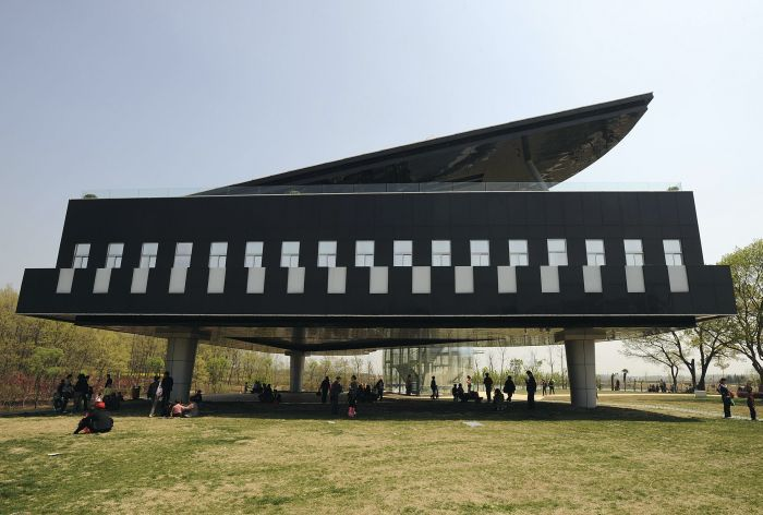 Visitors gather in front of and below a piano-shaped building in Huainan, Anhui province April 9, 2009. The building will be used as the Urban Planning Exhibition Hall.  REUTERS/Jianan Yu (CHINA ENTERTAINMENT SOCIETY)